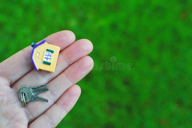 Hand holding house model and keys. Hand holding or giving small colorful house model and keys on green blurred grass background with copy space for text. Real royalty free stock images