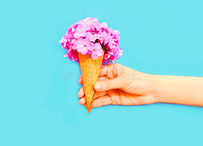 Hand holding ice cream cone with flowers over a blue background stock images