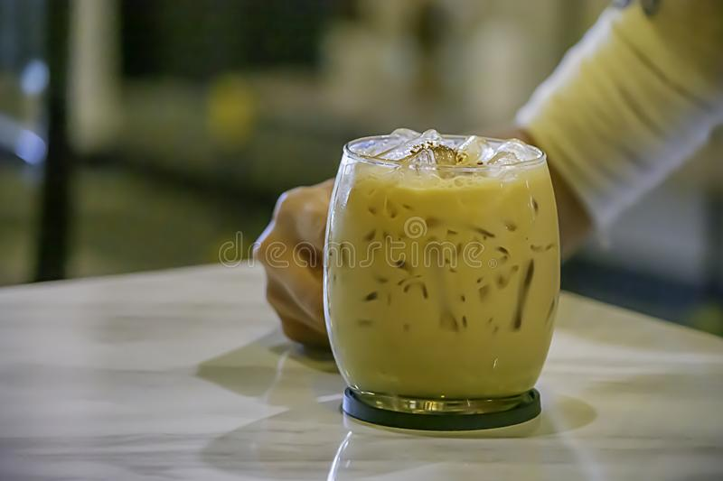 Hand holding Iced coffee in a glass on table stock photos