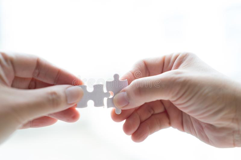 Hand holding jigsaw connecting to each other on Isolate white bac stock photo