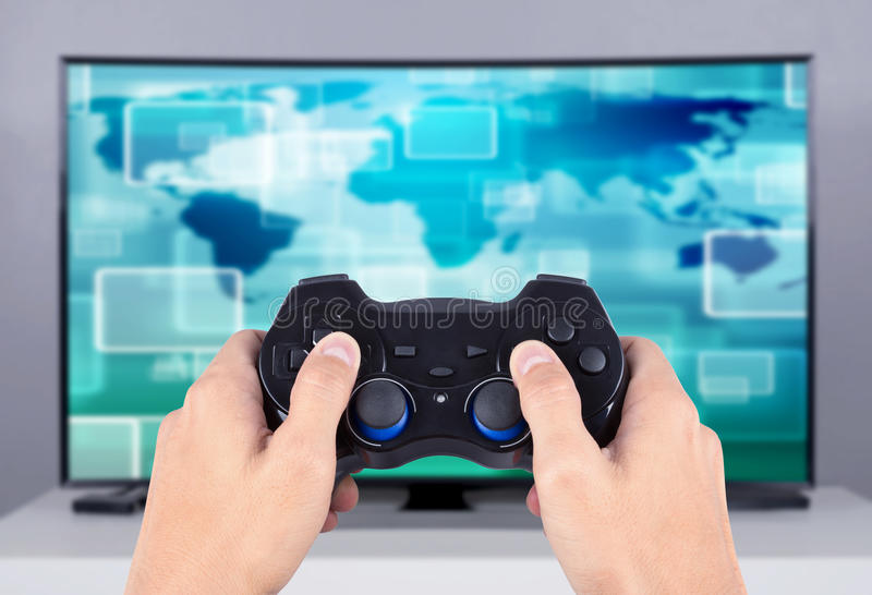 Hand holding joystick to playing video game on tv stock photos