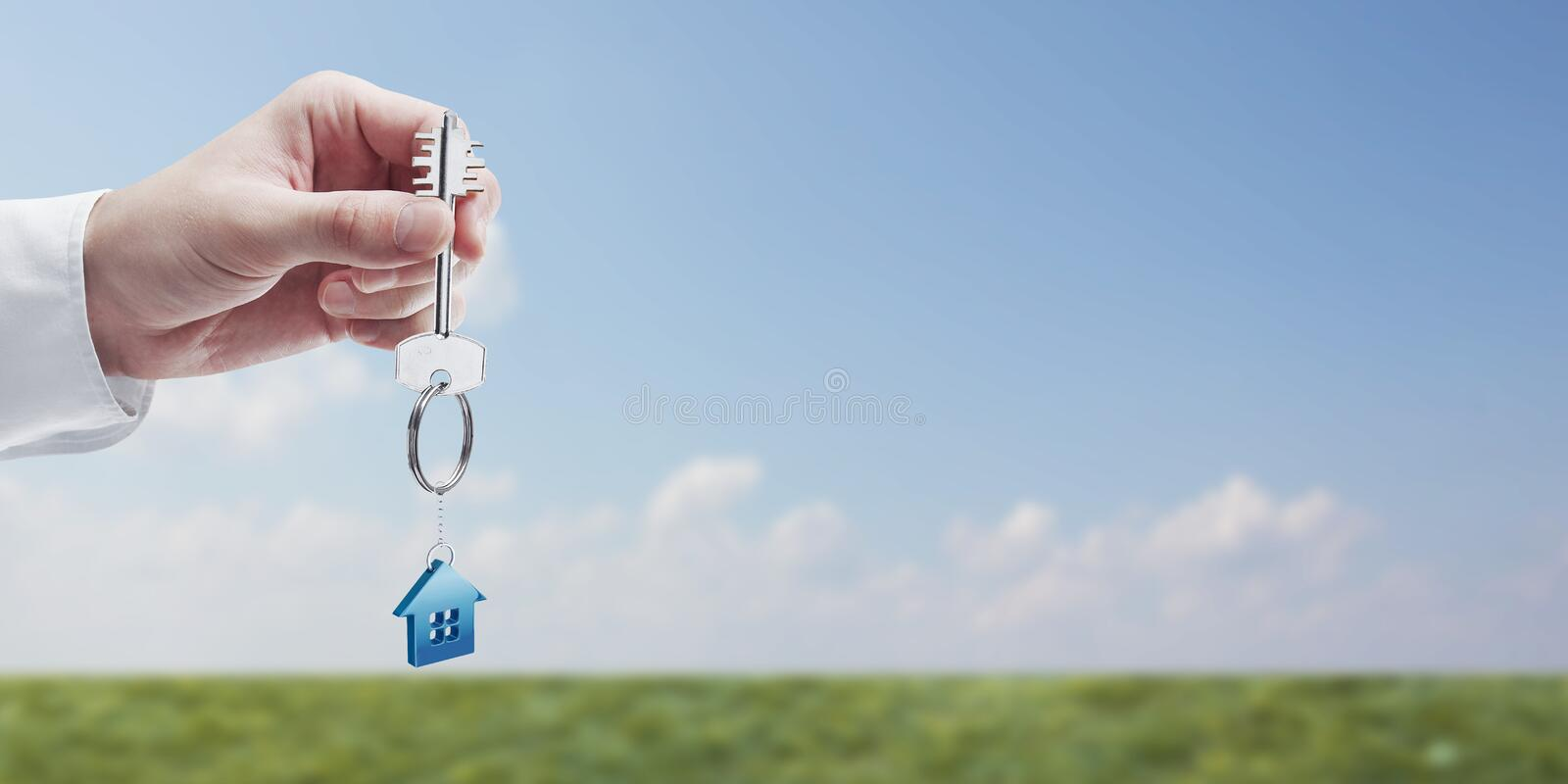 Hand holding key with a keychain. In the shape of the house. House key on background of nature stock image