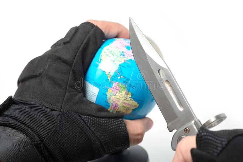 Hand holding knife ready to stab globe world map royalty free stock photography