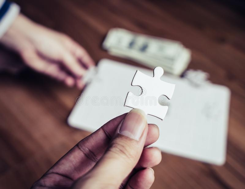Hand holding the last jigsaw for business competitive solution concept stock images