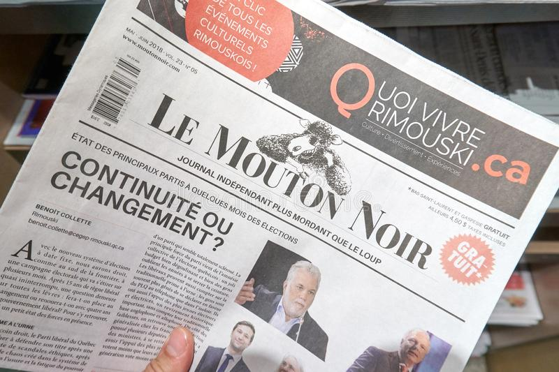 A hand holding Le Mouton Noir newspaper. MONTREAL, CANADA - SEPTEMBER 14, 2018: Le Mouton Noir newspaper in a hand royalty free stock photo