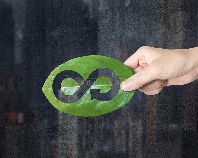 Hand holding leaf with hole of arrow infinity, circular economy stock image