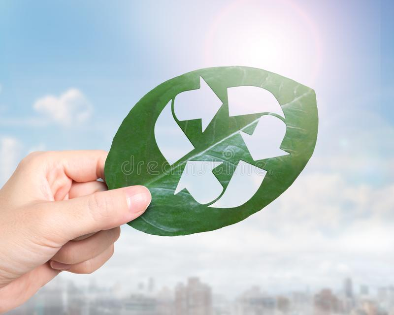Hand holding leaf with hole of recycling symbol, resource recovery stock photos