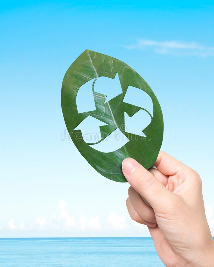 Hand holding leaf with hole of recycling symbol, resource recovery royalty free stock photography