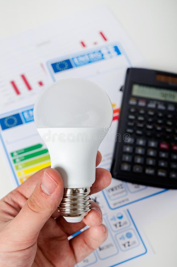 Hand holding LED bulb. Energy efficiency chart and calculator stock photo