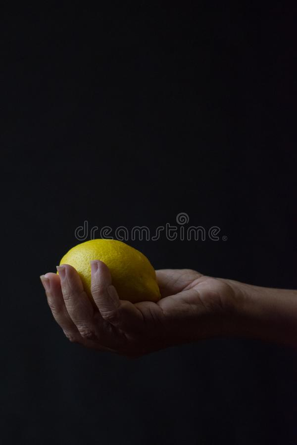 Hand holding lemon on black background royalty free stock photography
