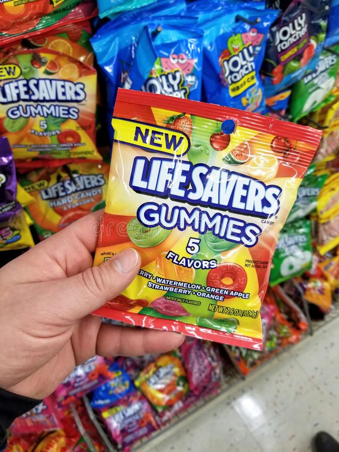 A hand holding Life Savers hard candy pack. PLATTSBURGH, USA - SEPTEMBER 10, 2018: A man holding Life Savers Gummies pack. Life Savers is an American brand of stock images