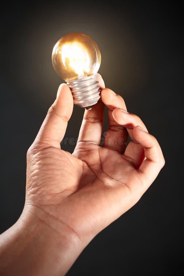 Hand holding light bulb stock image