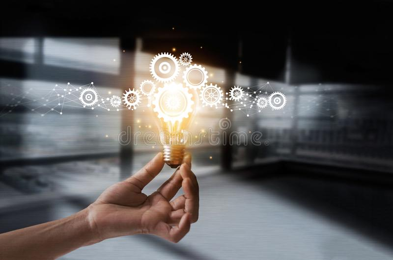Hand holding light bulb and cog inside. Idea and imagination stock photo