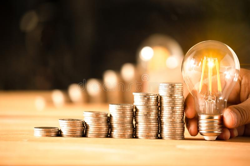 Hand holding a light bulb with coins stack royalty free stock images