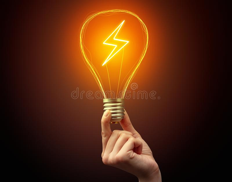 Hand holding light bulb on dark background. New Eco idea concept royalty free stock image