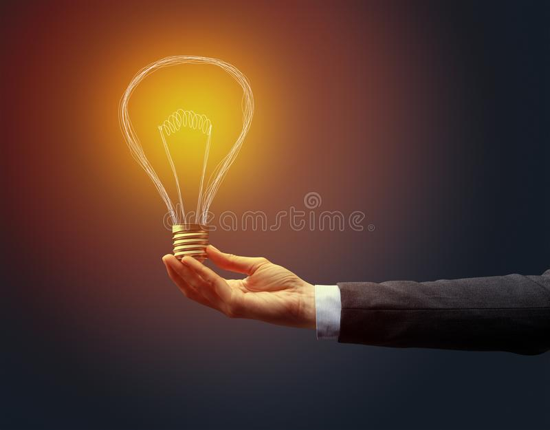 Hand holding light bulb on dark background. New idea concept royalty free stock photos