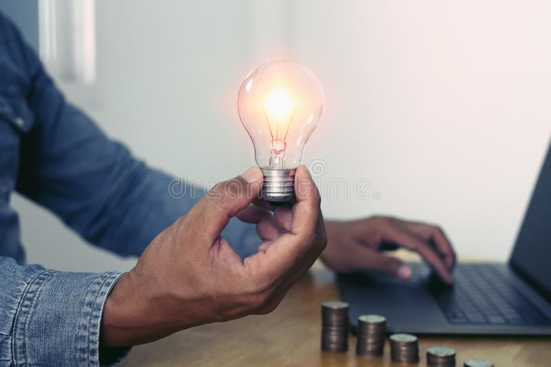 Hand holding light bulb with using laptop in office. concept saving energy power. Accounting, money, electricity, finance, business, lightbulb, save, knowledge royalty free stock photography