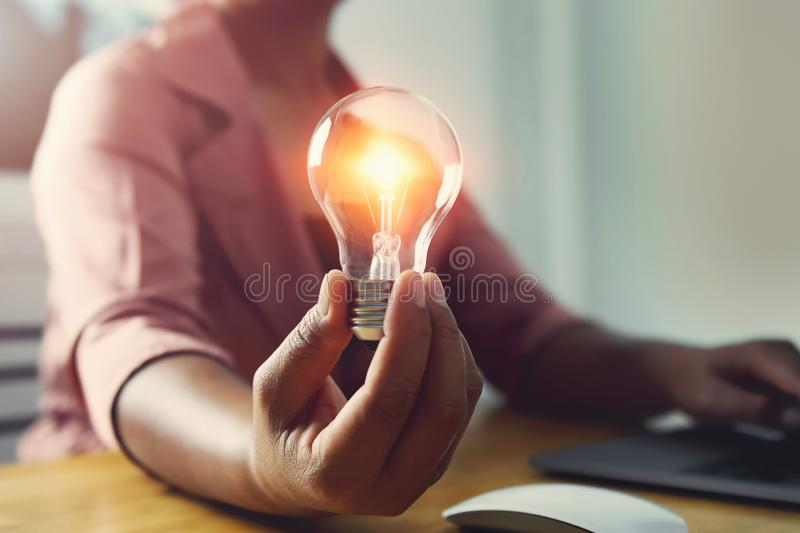 Hand holding light bulb with using laptop in office. concept saving energy power. Accounting, money, electricity, finance, business, lightbulb, save, knowledge royalty free stock photos