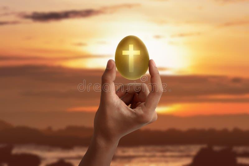 Hand holding the light of cross shape from the golden egg. At sunset stock image