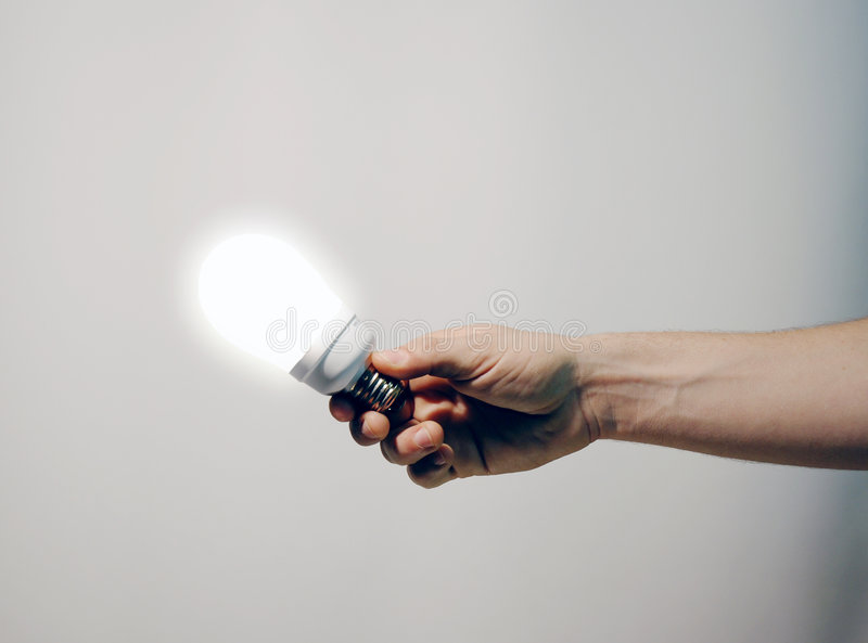 Hand holding lighted bulb royalty free stock photo