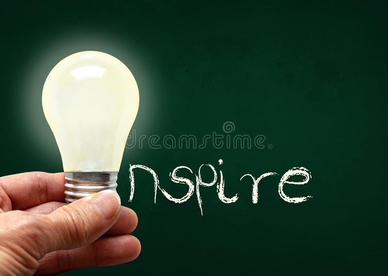 Hand Holding Lighted Bulb With Inspire on Chalk Board and Copy S. Man holding illuminated bulb with bare hands against chalkboard with the word Inspire. Concept royalty free stock photos
