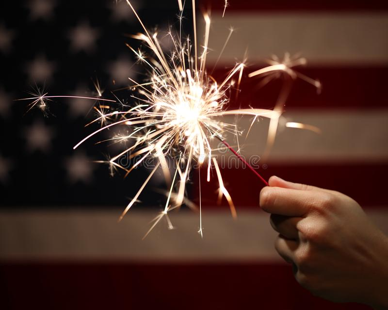 Hand holding lit sparkler in front of the American Flag for 4th of July stock photo