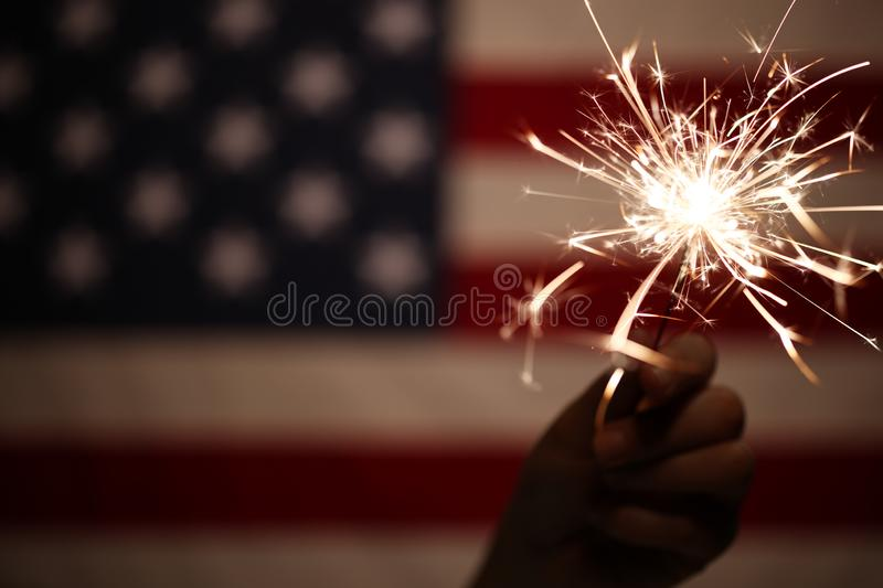 Hand holding sparkler in front of the American Flag for 4th of July celebration. Hand holding lit sparkler in front of the American Flag for 4th of July stock images