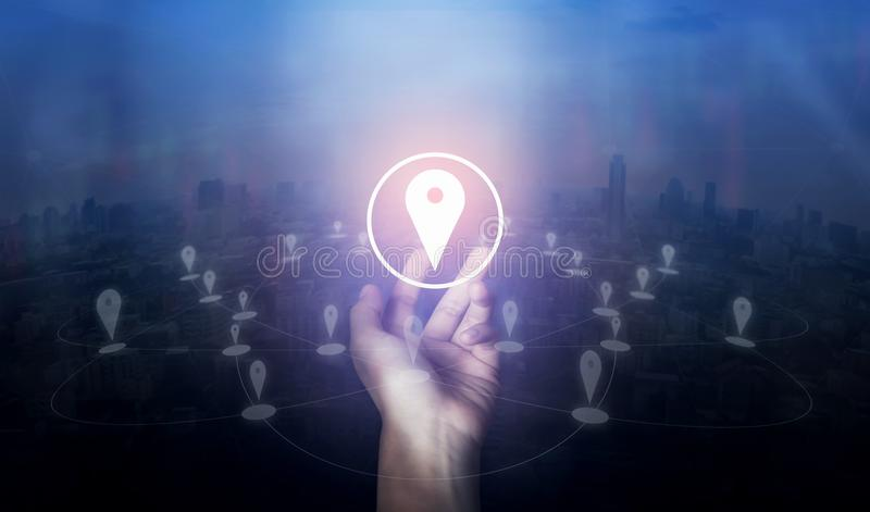 Hand holding location pin map icon and network connection on city of screen. royalty free stock images