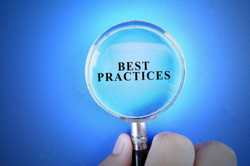 Hand holding magnify glass over a blue background with BEST PRACTICES words. Hand holding magnify glass over a blue background with BEST PRACTICES words stock photo