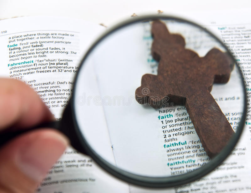 Hand holding magnifying glass. Focus on cross and word Faith royalty free stock photos
