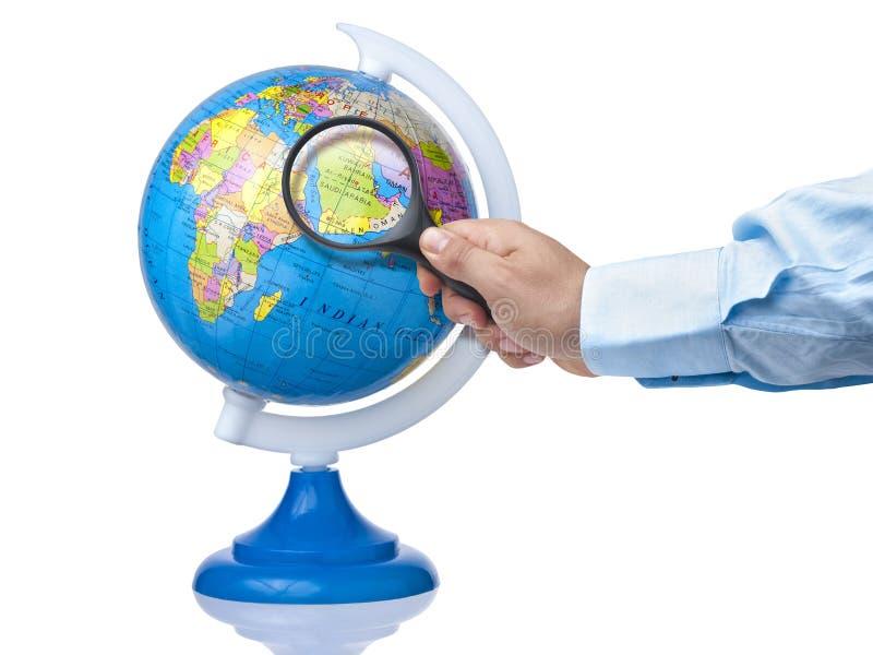 Hand holding magnifying glass on Arabian peninsula on globe isolated royalty free stock photos