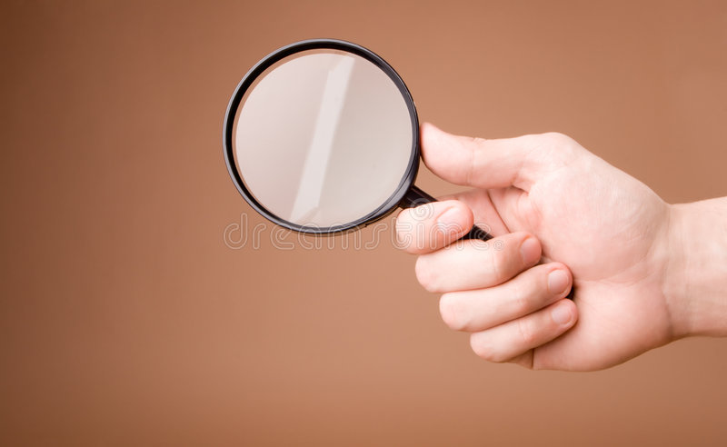 Hand holding magnifying glass on the beige background stock photography