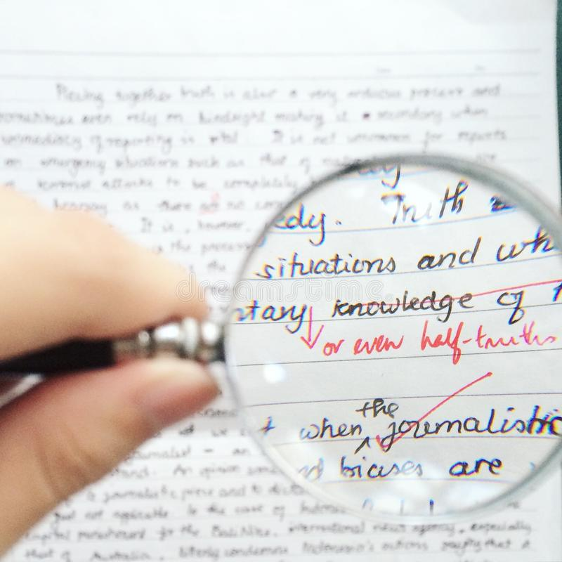 """Half Truths. Hand holding a magnifying glass over an essay with focus on the phrase """"or even half truths"""" stock photography"""