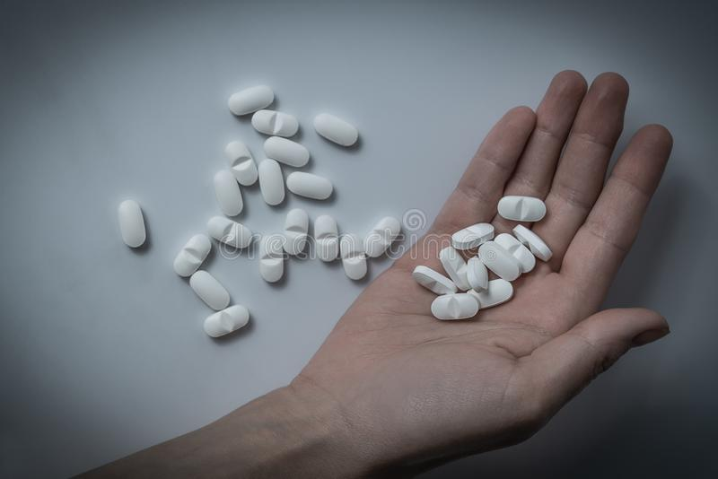 Hand holding many white prescription drugs, medicine tablets or vitamin pills in a pile - Concept of healthcare, opioids addiction stock image