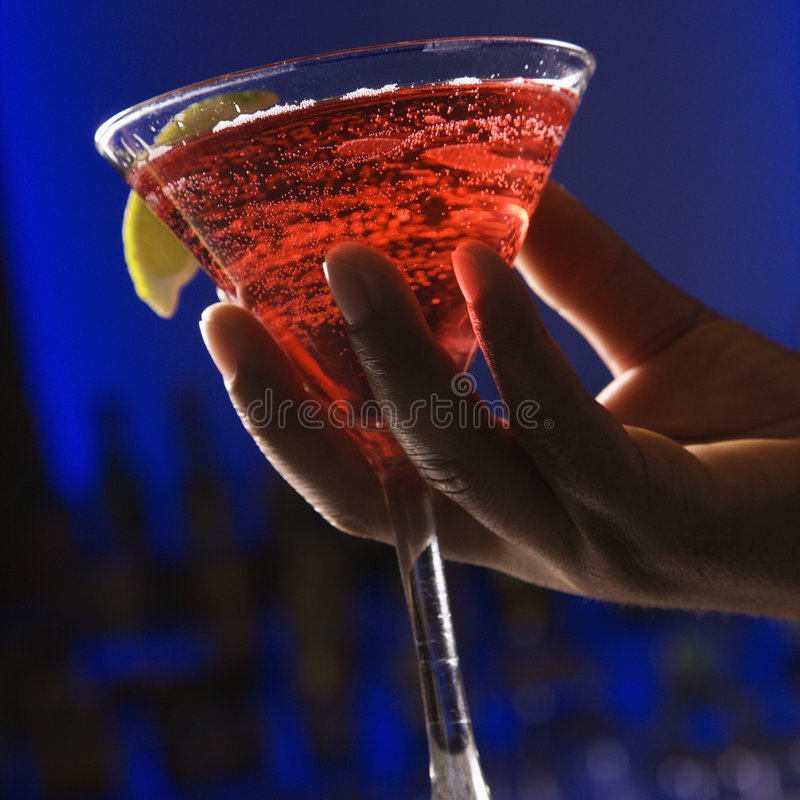 Hand holding martini. stock image