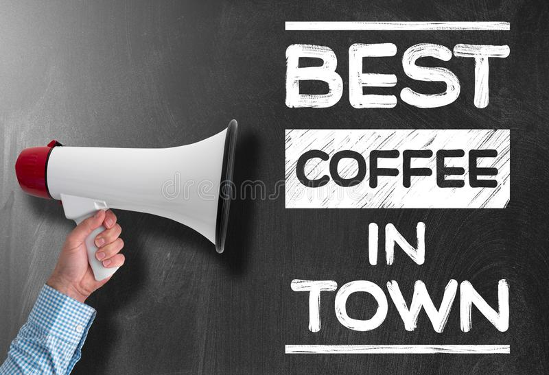 Hand holding megaphone against blackboard with text BEST COFFEE IN TOWN. Hand holding megaphone or bullhorn against blackboard with text BEST COFFEE IN TOWN royalty free stock image