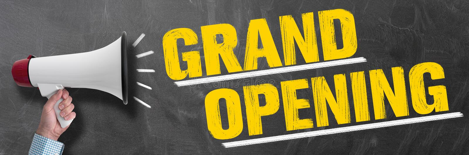 Hand holding megaphone or bullhorn against blackboard with text GRAND OPENING stock photos