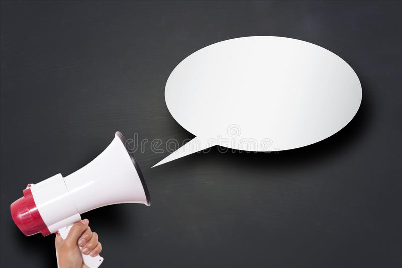 Hand Holding Megaphone with Speech Bubble. Hand holding megaphone agains blackboard with speech bubble, announcement marketing concept loud communication stock photos