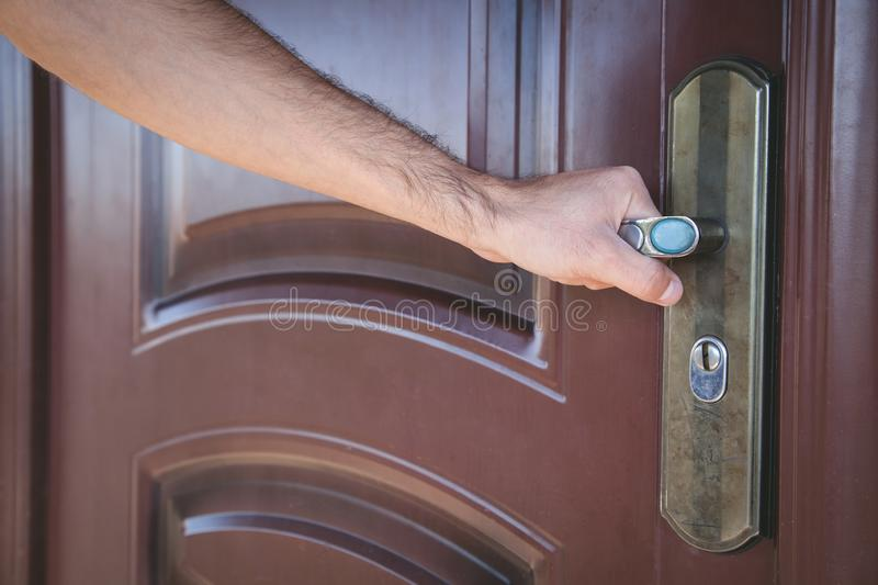 Hand holding a metal handle in the door stock photography