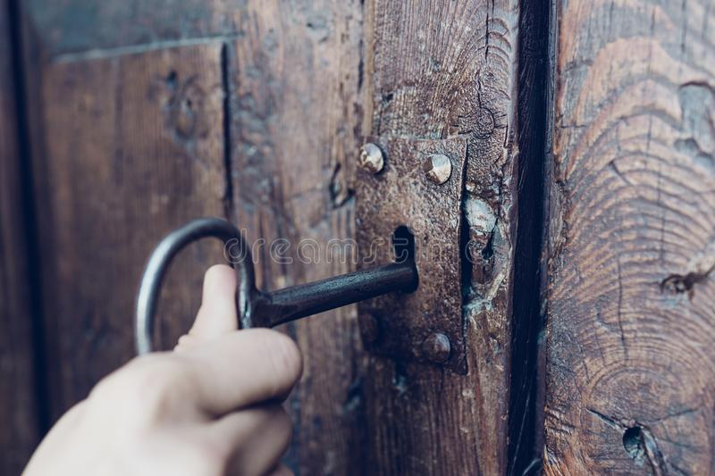 Hand holding metal vintage key to unlocking old secret wooden do royalty free stock photography