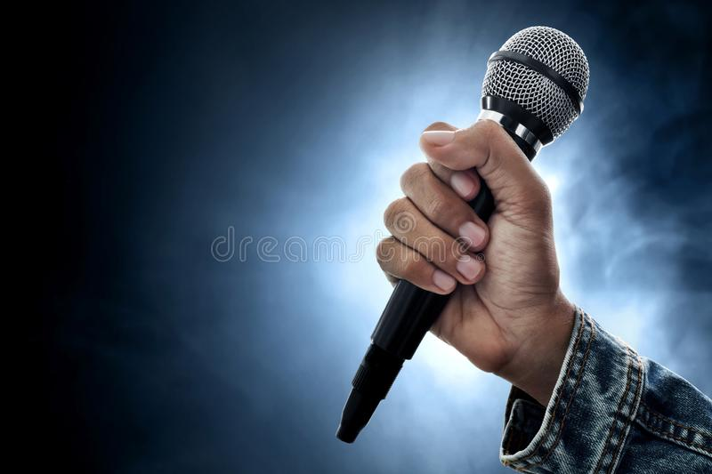 Hand holding microphone on smoke background. Hand hold microphone on smoke background stock photography