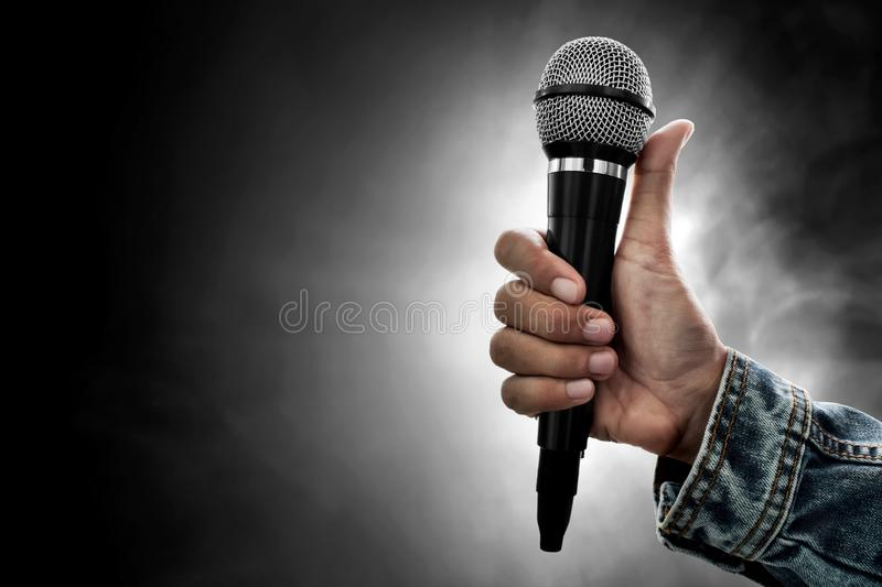 Hand holding microphone on smoke background. Hand hold microphone on smoke background royalty free stock images