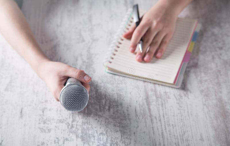Hand holding microphone and writing on notepad stock image