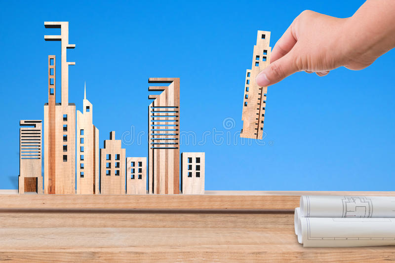 Hand holding miniature building wood model on blue background. Real estate concept stock photo