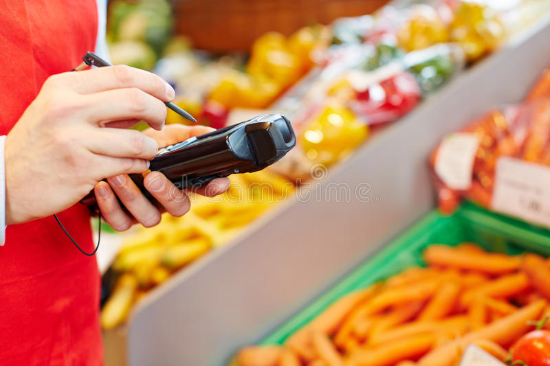 Hand holding mobile data. Registration terminal in a supermarket stock image