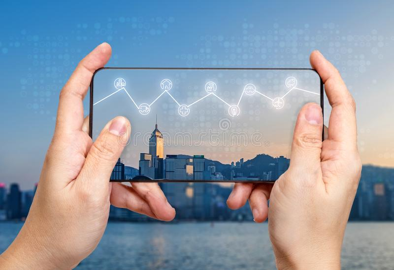 Hand holding mobile with Internet of things iot word on screen with icon feature glowing in air with blur city building stock images