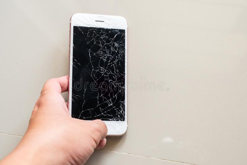 Hand holding mobile phone with broken glass screen. Man Hand holding mobile phone with broken glass screen stock image