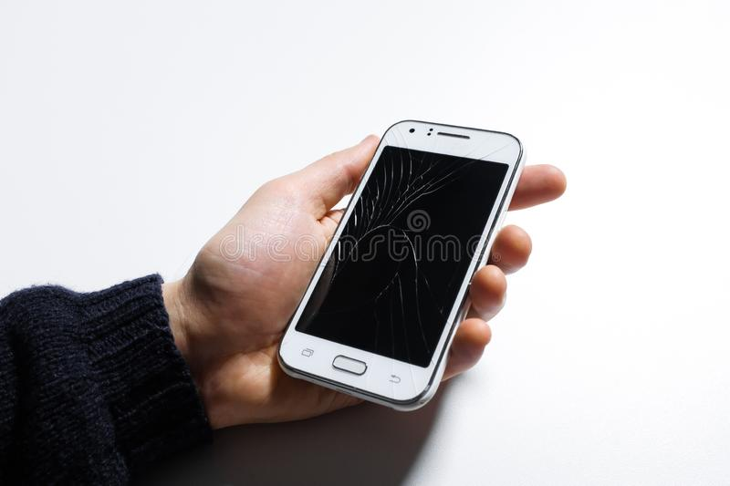 Hand holding mobile phone with broken screen on white background.  royalty free stock photo