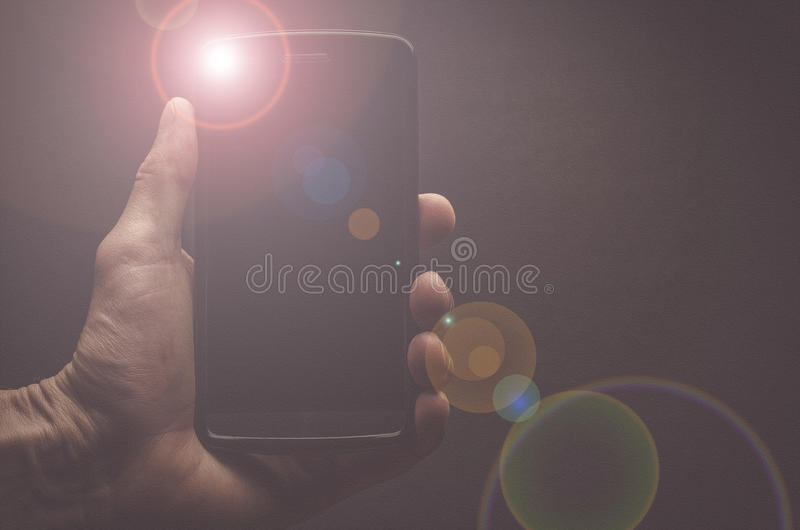 Hand holding a mobile phone with flash royalty free stock photos
