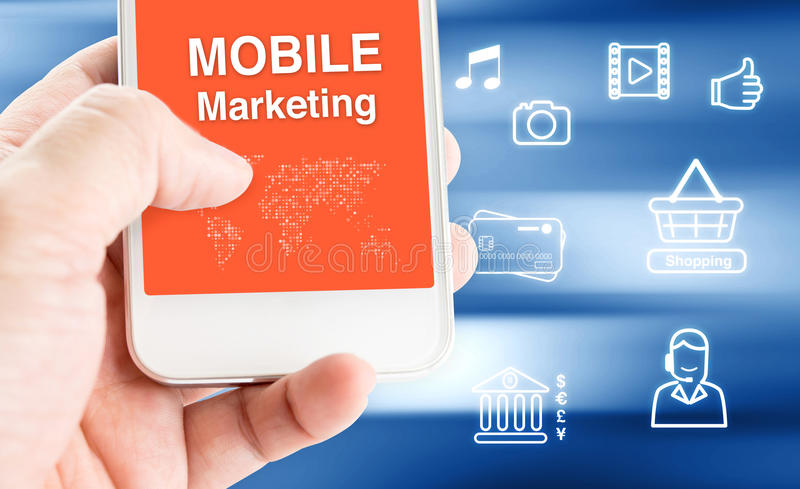 Hand holding mobile phone with MOBILE MARKETING word with relate. D icon on motion blue blur background,Digital Marketing concept stock images